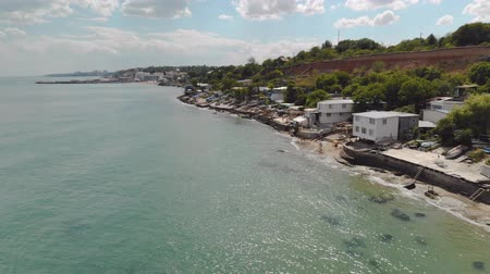 hırvatistan : Aerial view of the sandy coast with green-blue water and buildings near the beach. Coastline with vacationing tourists. The concept of the resort area on the sea cliff Stok Video