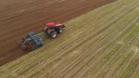 solo : Aerial view of a powerful energy-saturated tractor with a large hook force, performing tillage for sowing winter crops with a disc cultivator in the autumn Stock Footage