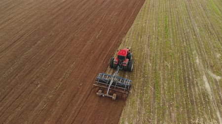 saturado : Aerial view of a powerful energy-saturated tractor with a large hook force, performing tillage for sowing winter crops with a disc cultivator in the autumn Vídeos