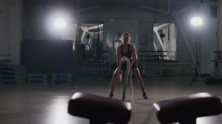 kardio : Steadicam shot of a beautiful young Caucasian girl in a dark gym doing crossfit with two ropes. The concept of a healthy lifestyle