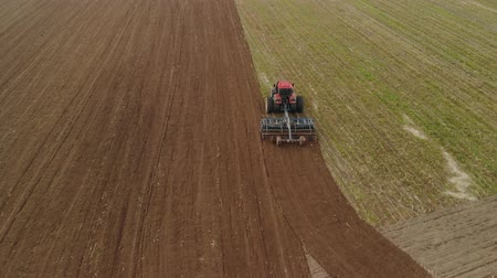 powerful : Aerial view of a powerful energy-saturated tractor with a large hook force, performing tillage for sowing winter crops with a disc cultivator in the autumn Stock Footage