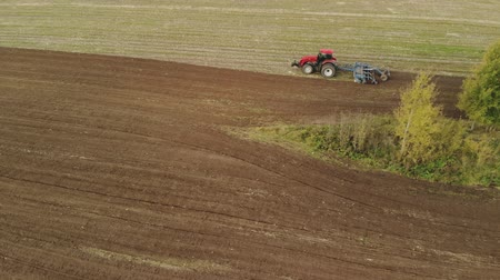 engine : Aerial view of a powerful energy-saturated tractor with a large hook force, performing tillage for sowing winter crops with a disc cultivator in the autumn Stock Footage