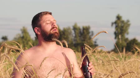 göğüs : Tanned bearded man with a bare torso drinks beer with pleasure from a dark bottle against the background of a barley field, the excess of the drink flows down his facial hair Stok Video