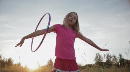 mókás : Slow motion of a cute, funny girl in pink clothes spinning a gymnastic Hoop on her right hand in Sunny summer weather. A child plays with a hula Hoop at sunset
