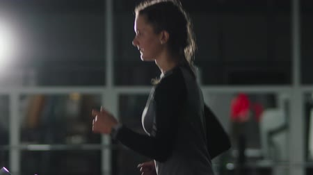 ginásio : Portrait of a pretty athletic brown-haired woman with a ponytail on her head and a fitness bracelet, engaged in physical culture on a treadmill in a dark room of the gym. Motivation for a healthy lifestyle