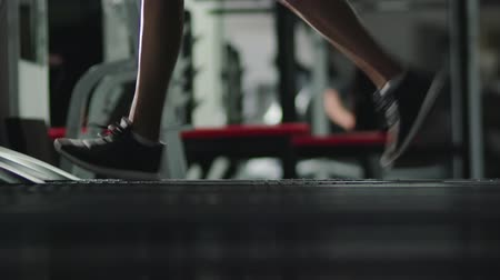 ginásio : Legs of a pretty slender girl in sports shoes engaged in physical training on a treadmill in a dark room of the gym. Motivation for a healthy lifestyle