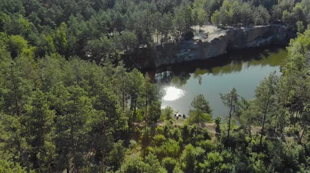 montanhas rochosas : Beautiful lake with dark green water in a rocky canyon. Top view of a high, stone cliff surrounded by coniferous forest Stock Footage