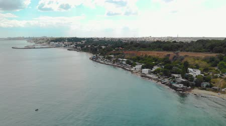 tyrkysový : Aerial view of the sandy coast with green-blue water and buildings near the beach. Coastline with vacationing tourists. The concept of the resort area on the sea cliff Dostupné videozáznamy