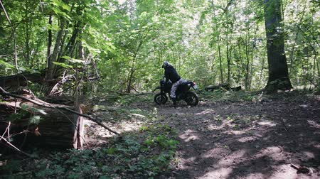enduro : Rider in motobots and spotted pants puts on helmet on his head, sits on a black off-road motorcycle and begins the trip, starts with a slip of the rear wheel in the forest area. Extreme entertainment