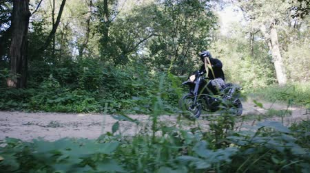 ciclismo : Biker in protective gear extreme rides on an off-road motorcycle through the forest, passes the turn with a skid on a sandy country road. Concept of outdoor activities