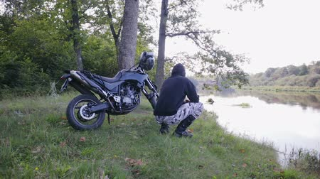 squatting : Steadicam shot a rider in motorcycle boots, spotted pants and a black hoodie squatting beside an off-road motorcycle and admiring the view of a picturesque river in Sunny autumn weather. The concept of active fun in the fresh air Stock Footage