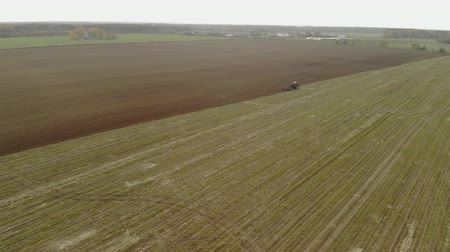 engine : Aerial view of a farmer in a modern energy rich red tractor cultivating fertile soil for sowing crops attached to a blue cultivator in the autumn period of the year Stock Footage
