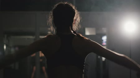ginásio : Steadicam shot of a slender pretty Caucasian girl training the muscles of the shoulders and back on a multifunctional simulator in a dark room of the gym. Motivation to sport, healthy lifestyle