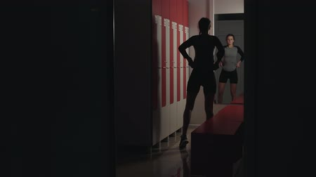тренер : A young, beautiful athlete in leggings and a t-shirt prepares for training, adjusts her hair and poses in front of a mirror in a darkened locker room. A healthy lifestyle, movement, beautiful athletic body