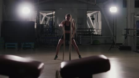 kardio : A young girl in a sports black top and leggings conducts training with combat ropes in the hall. The athlete swings the ropes in a wave motion as part of a burning warm-up, firmly demonstrating her strength. Fitness for health