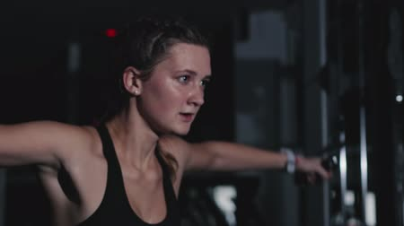 delgado : Steadicam shot of a slender pretty Caucasian girl training the muscles of the shoulders and back on a multifunctional simulator in a dark room of the gym. Motivation to sport, healthy lifestyle