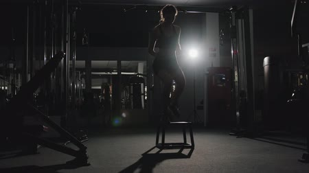 kardio : Cute slender Caucasian girl is engaged in high-intensity interval training in a dark gym. The concept of modern strength training, fat burning and healthy lifestyle Dostupné videozáznamy