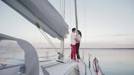 iatismo : Slow motion of two young people in love, a guy and a girl in glasses, hugging standing on the bow of a white yacht during a calm on the lake in the evening Sunny weather in summer. Honeymoon concept