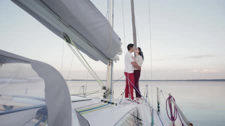 vessels : Slow motion of two young people in love, a guy and a girl in glasses, hugging standing on the bow of a white yacht during a calm on the lake in the evening Sunny weather in summer. Honeymoon concept
