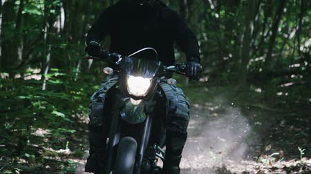 enduro : A rider on a black off-road motorcycle with the headlight on sweeps past with his leg stretched out to the side, a layer of dust and dry leaves rises from under the wheels. The concept of extreme entertainment
