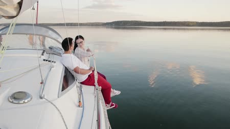 iatismo : Two young people in love, a couple in red pants sitting on Board a white sailing yacht dangling his legs down, floating in the dark calm water. The concept of honeymoon, travel Stock Footage