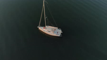 plachta : Aerial view of two young people in love, a married couple in red pants sitting on the bow of a white sailing yacht drifting in dark calm water. The concept of honeymoon, travel