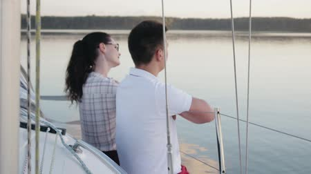 plachta : Two young people in love, a couple in red pants sitting on Board a white sailing yacht dangling his legs down, floating in the dark calm water. The concept of honeymoon, travel Dostupné videozáznamy