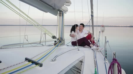 iatismo : Slow motion loving couple enjoying each other and sunset from the deck of a sailing boat moving in a calm sea. Honeymoon concept Stock Footage