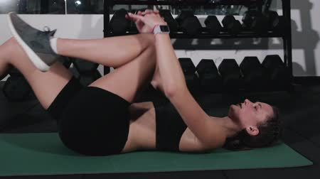 растягивание : Athlete dressed in black sportswear, lying on the floor pulls her knees to her chest, flexible stretching of the body after a functional workout Стоковые видеозаписи