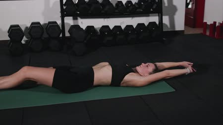 sakk : Athlete dressed in black sportswear, lying on the floor pulls her knees to her chest, flexible stretching of the body after a functional workout Stock mozgókép