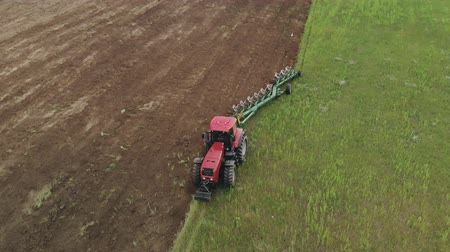 saturado : Aerial view of a farmer on an energy-saturated tractor with a large hook force producing plowing with a turnover of the soil layer with a modern plow in cloudy weather. The concept of agribusiness