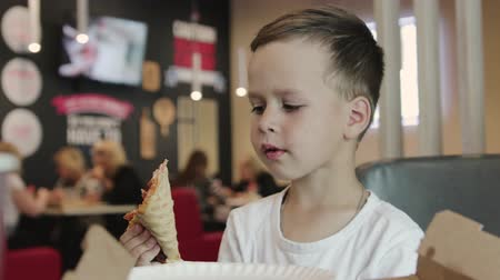 mókás : Portrait of a joyful, little boy in a white t-shirt, who sits at a table in a cafe and eats pizza. He holds a large slice of pizza and laughs merrily