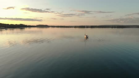 kapcsolat : A happy, young couple a woman and a man stand together and embrace on a sailing boat at sunset, which floats on the lake, from a birds eye view. Beautiful nature around Stock mozgókép