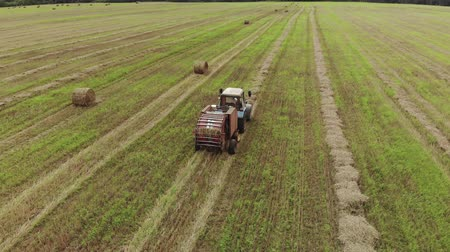 rulolar : Aerial view of a tractor producing straw pressing on a harvested agricultural field. From the trailer baler comes ready roll