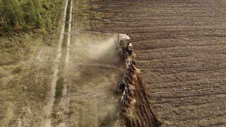 akkerland : Aerial shot of a powerful tractor with a plow cultivating the field and raising huge clouds of brown suffocating dust on the agricultural field. The concept of a dry lean year, soil erosion