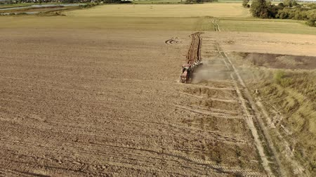 földműves : Aerial shot of a powerful tractor with a plow cultivating the field and raising huge clouds of brown suffocating dust on the agricultural field. The concept of a dry lean year, soil erosion