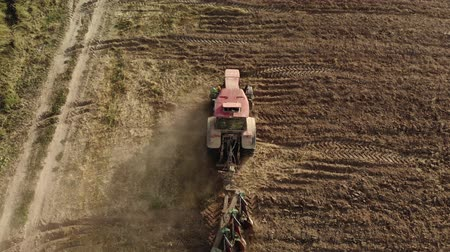 powerful : Aerial shot of a powerful tractor with a plow cultivating the field and raising huge clouds of brown suffocating dust on the agricultural field. The concept of a dry lean year, soil erosion