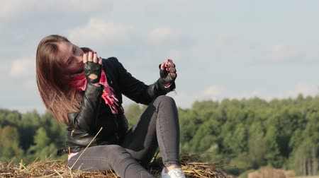 szalma : A beautiful girl of European appearance in a black leather jacket and a red handkerchief sits on a roll with straw in the field, enjoying and looking into the distance squinting against the blue sky. Freedom, desire to live