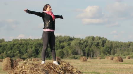 rulolar : A beautiful woman of European appearance in a black leather jacket and a red scarf stands on a roll of straw in a field, enjoying and looking into the distance squinting against the blue sky. She spread her arms and closed her eyes. Freedom, desire to liv Stok Video