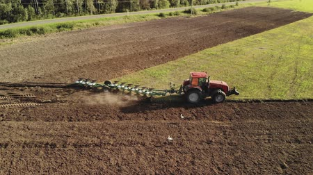 furrow : Aerial side view of a modern red tractor with tillage unit preparing dark fertile brown soil. The farmer plows the land for sowing. The concept of agribusiness