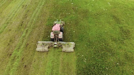 çiftlik hayvan : Aerial view of tractor rear cutting fresh green grass on silage and haylage on pasture for use as animal feed on farm. The concept of agribusiness