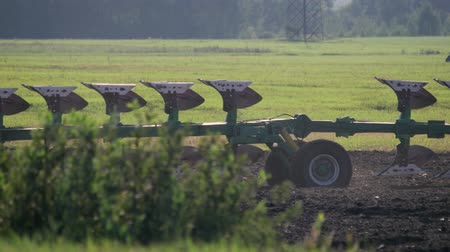 technics : Close-up of a reversible plow with many ploughshares on support wheels moving behind a tractor in an agricultural field with bushes. Plowing the land for sowing in the spring