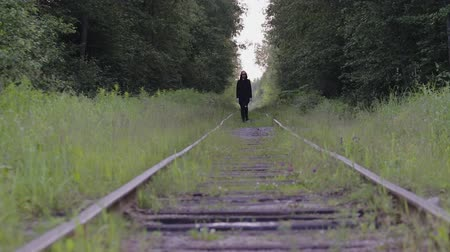 osamělost : Panorama of railway tracks, on which confidently is a man in black clothes and sunglasses, behind the train in the woods. The actor plays his part well