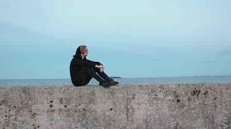 osamělost : A young, stylish guy, a model in black clothes and sunglasses sits on a stone, old pier. The man looks at the sea and relaxes