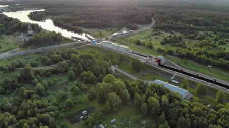 çimenli yol : Russia, Povenets-26 JUNE 2019. Aerial view of a white cruise ship passing the narrow gateway of the white sea-Baltic canal in Karelia. The concept of navigation on the Northern sea route Stok Video