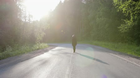aventura : Steadicam shot of a Caucasian guy in a black hooded cardigan and sunglasses walking in the middle of a country road with asphalt pavement surrounded by forest at sunset. Travel concept, self-search