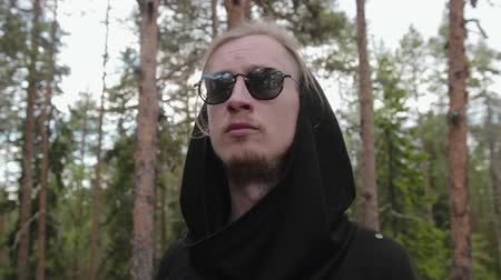 ориентация : Steadicam circular motion of a stylish young European guy in a dense forest. A man in a black hooded cardigan looks around the area with a reflection in his sunglasses. Travel concept