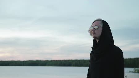 сочетание : A young, handsome guy in a black hoodie and glasses walks confidently against the horizon, an amazing combination of heaven and water. Freedom and the concept of adventure