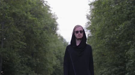 concentrato : Portrait of a handsome, young man, blond with a beard in dark glasses and a black cardigan, confidently walking forward against the background of green leaves, bokeh. Model gait, outdoor shooting
