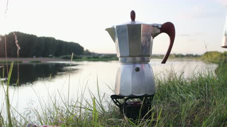 geiser : Morning coffee in an open camp on the river Bank. Hand puts geyser coffee maker on the burner burning Primus, next to sets a metal mug for invigorating drink. The concept of rest in travel